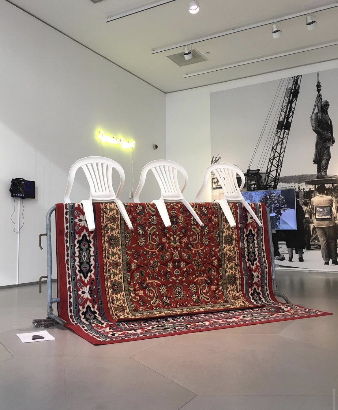 Installation View, She doesn't wear earrings till this day, 2020, barricade, rugs, plastic chairs, marble, text, dimensions variable