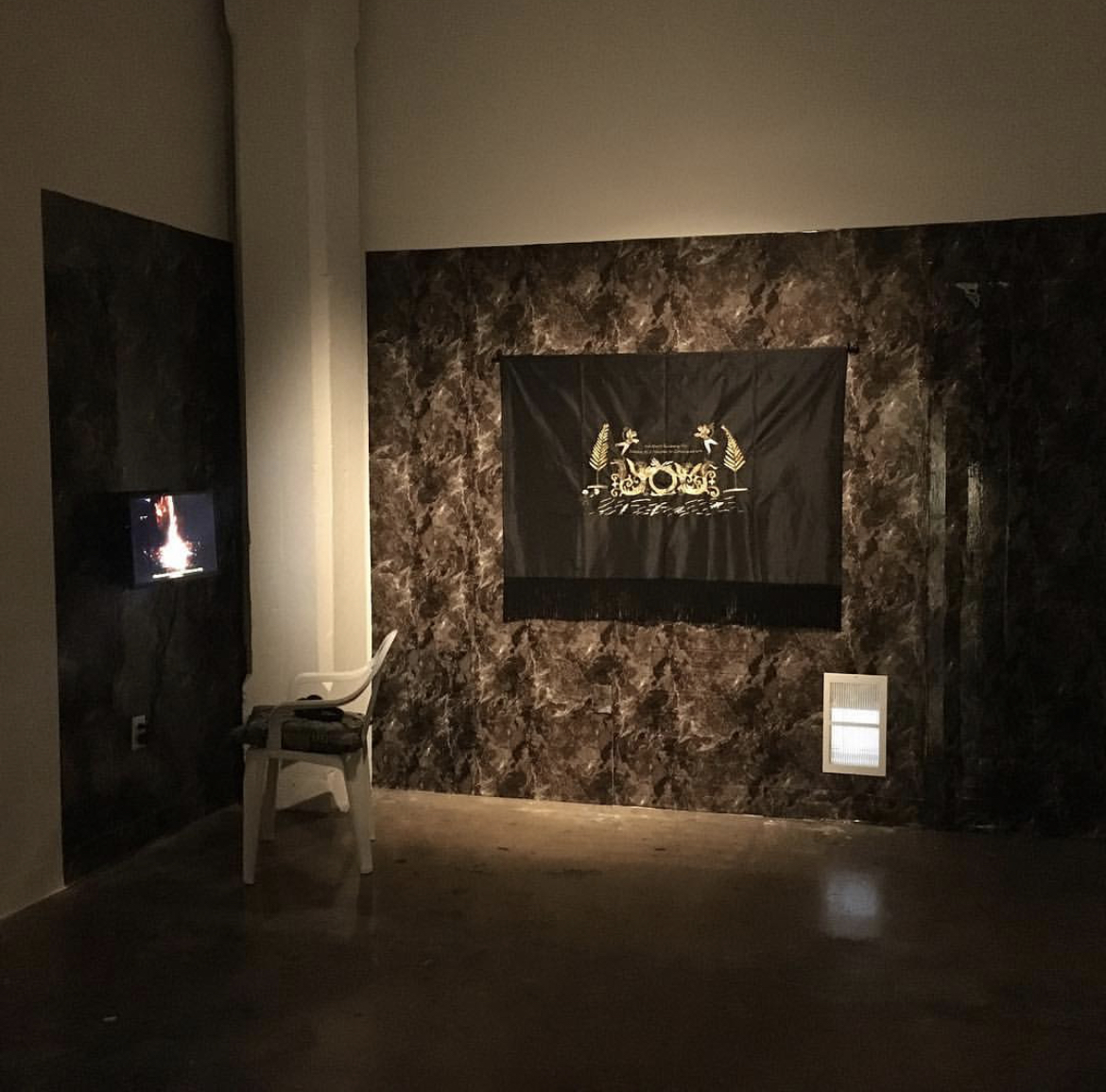 Installation view, Uncanny Gardening II, wallpaper, gesso resin and graphite on a wood panel, gold thread on silk, single channel video, plastic chair, embroidered pillow